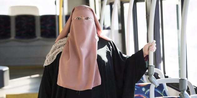 Quebec woman Warda Naili poses for a photograph on a city bus in Montreal on October 21, 2017.