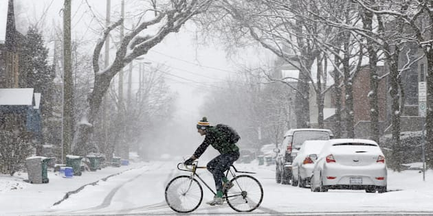 A man rides a bicycle during a spring snow storm in Ottawa, April 6, 2016.