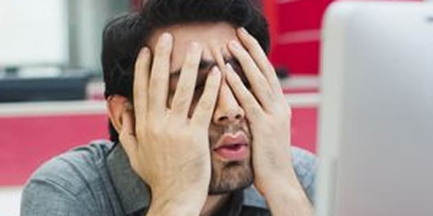 Businessman covering his face with hands