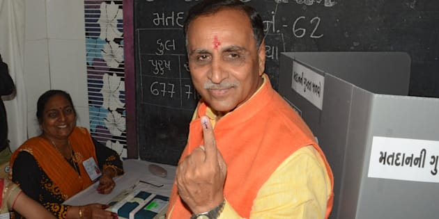 Gujarat state Chief Minister Vijay Rupani shows his inked finger after casting his ballot during the first phase of Vidhan Sabha elections of Gujarat state at Rajkot, some 220 kms from Ahmedabad on December 9, 2017.