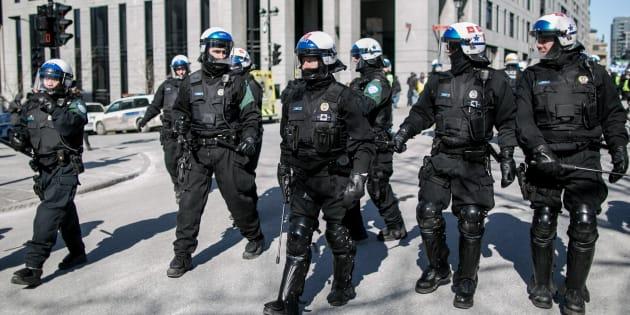 La police de Montréal monte la garde devant l'hôtel de ville durant une manifestation.