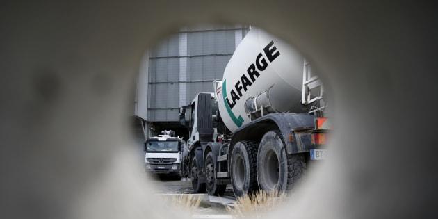 Un camión de cemento se ve a través de un agujero en una pared en la planta de producción de Lafarge en Pantin, en las afueras de París.