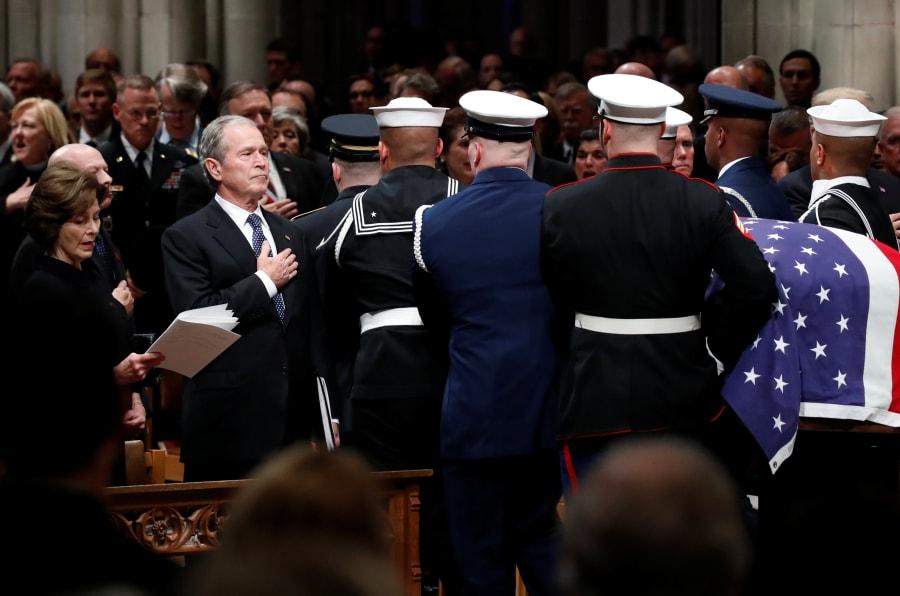 El expresidente George W. Bush coloca su mano sobre su corazón al paso del ataúd del expresidente George H.W. Bush cubierto con la bandera de EU, que es llevado por una guardia de honor militar de servicios conjuntos después del funeral de estado en la Catedral Nacional en Washington. A la izquierda está su esposa Laura Bush.