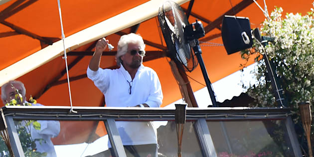 TOPSHOT - Five Star Mouvement (M5S) founder Beppe Grillo shows a silver bell from a hotel's roof garden in downtown Rome, on June 2, 2018, during a ceremony to mark the anniversary of the Italian Republic (Republic Day). (Photo by Alberto PIZZOLI / AFP)        (Photo credit should read ALBERTO PIZZOLI/AFP/Getty Images)