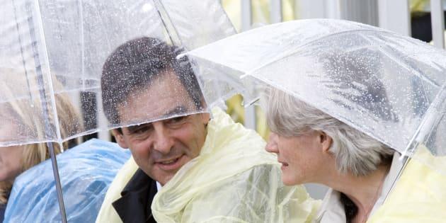 François Fillon, ici sous la pluie avec sa femme lors d'un déplacement au Canada, doit-il craindre la météo?