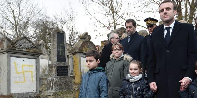 Emmanuel Macron tient la main d'enfants au moment où il visite le cimetière juif profané de Quatzenheim, en Alsace, le 19 février 2019.