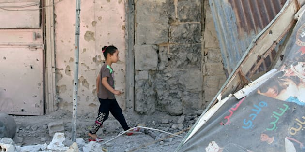 Una niña camina entre escombros en la parte rebelde de la ciudad de Deraa, al sur de Siria, durante la tregua acordada entre EEUU y Rusia.