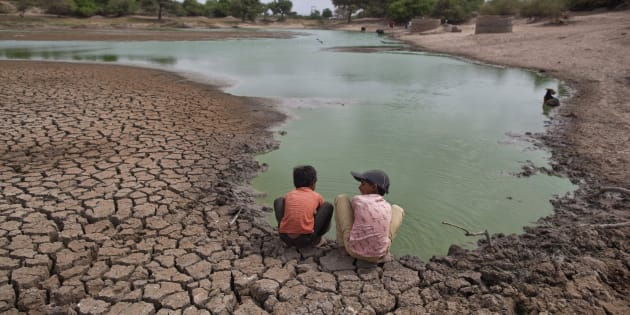 Children wash their hands in a partially dried-out natural pond at Badarganj village, in the western Indian state of Gujarat, August 5, 2012.