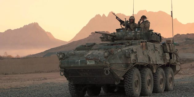 A Canadian LAV (light armoured vehicle) arrives to escort a convoy at a forward operating base near Panjwaii, Afghanistan at sunrise on Nov.26, 2006.