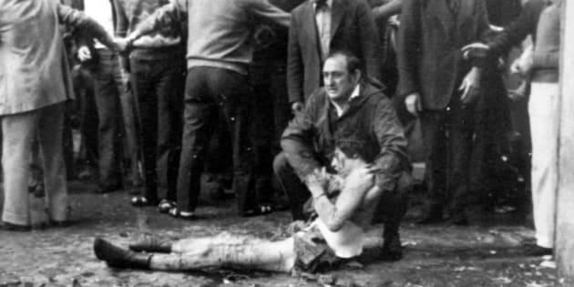 Un operaio soccorre uno dei feriti dell'attentato a piazza della Loggia a Brescia il 28 maggio 1974