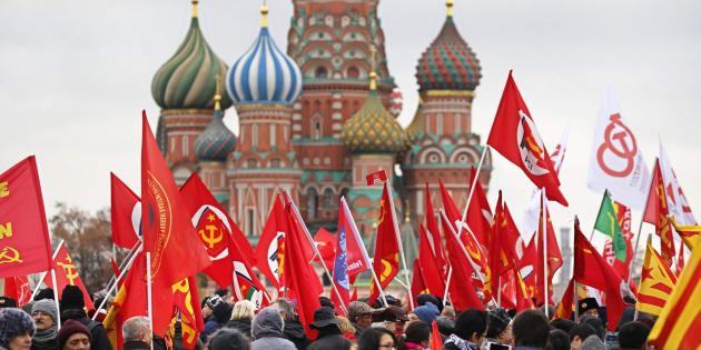I comunisti russi innalzano la bandiera rossa dei Soviet davanti al Mausoleo di Lenin nella Piazza Rossa di Mosca