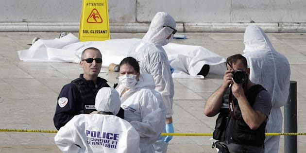 Investigative police officer work by a body under a white sheet outside Marseille 's main train station Sunday, Oct. 1, 2017 in Marseille, southern France