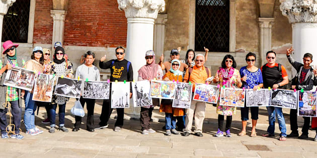 Indonesian tourists hold up photographs of Kolkata in Rome as part of The Sainthood Project.