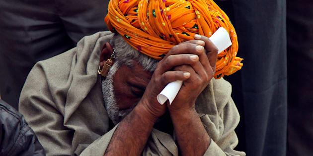 File photo of a man sitting in a queue to deposit his old high denomination notes in Ajmer.