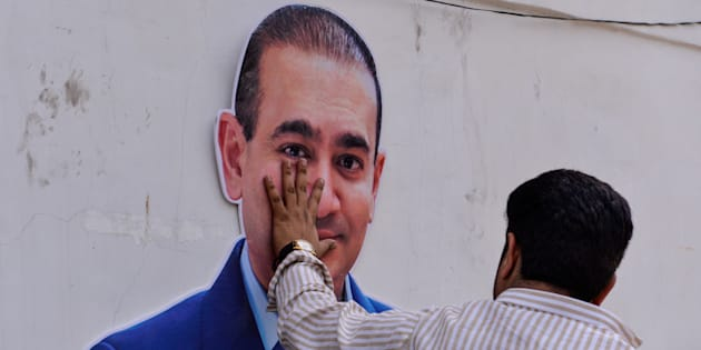An Indian supporters of the Congress Party keeps his hand on the face of a cut out of billionaire jeweler Nirav Modi during a protest in New Delhi on February 16, 2018.