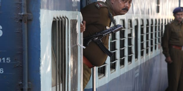 A Railway Police personnel peeps out from the door of a special passenger train at a railway station in Chandigarh.