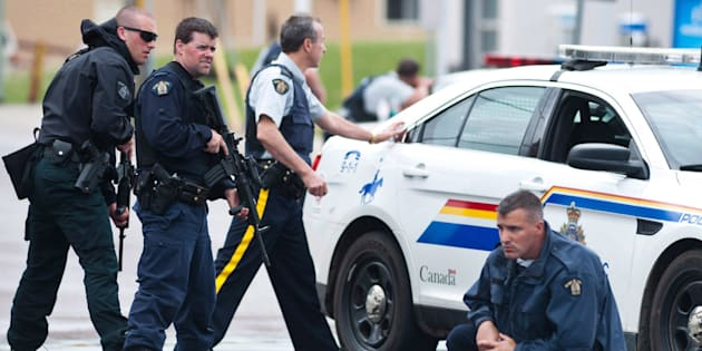 Police keep watch on a house as they search for a heavily armed gunman following the shooting of three Mounties in Moncton, N.B., on June 5, 2014.