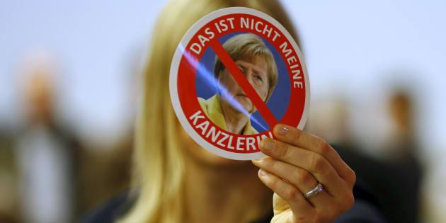 Una sostenitrice dell'ala destra del partito AfD regge uno sticker con il volto della Cancelliera Angela Merkel al congresso di Hannover nel 2015