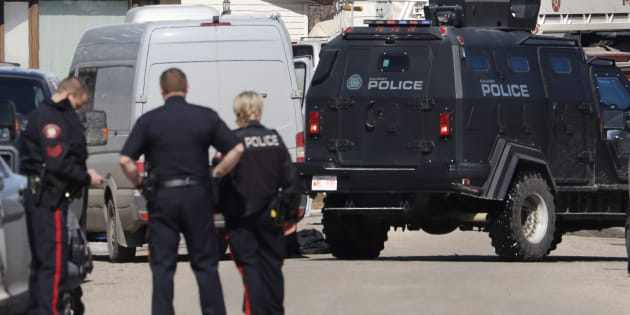 Calgary police officers stand at the scene of a shooting on March 27, 2018.