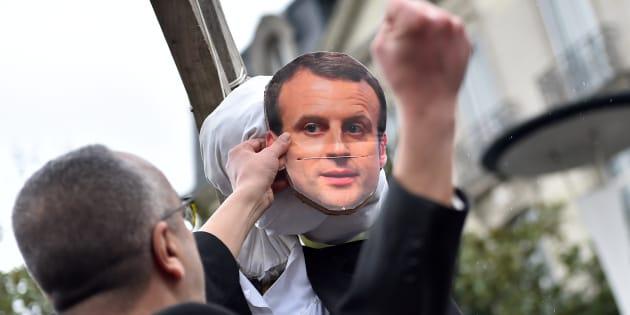 Un homme frappant le mannequin à l'effigie du président Macron pendant une manifestation à Nantes.