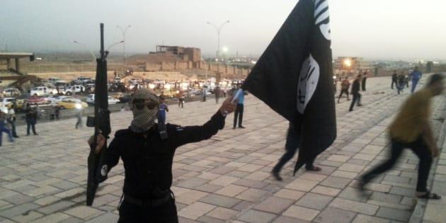 Un soldat de Daech brandit un drapeau de l'EI à Mossoul en Irak, en juin 2014.