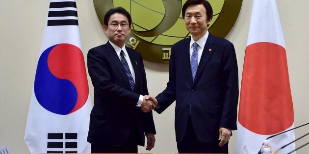 2015年12月28日、慰安婦問題の日韓合意を結んで握手する岸田外相(左)と韓国の尹炳世外相