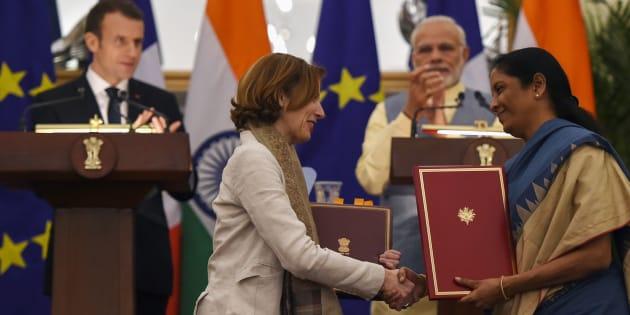Le Premier ministre Narendra Modi (à droite à l'arrière-plan), le Président Emmanuel Macron (à gauche à l'arrière-plan), la Ministre de la Défense indienne Nirmala Sitharaman (à droite) et la Ministre de la Défense Florence Parly (à gauche) signent un accord bilatéral à New Delhi le 10 mars 2018.