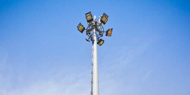 Circle of bulbs, cell phone gsm antennas on tall metal pole.