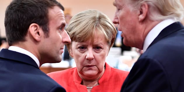 French President Emmanuel Macron, German Chancellor Angela Merkel and U.S. President Donald Trump confer at the start of the first working session of the G20 meeting in Hamburg, Germany, July 7, 2017. REUTERS/John MacDougall/Pool