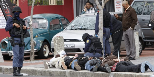 Police stand over six suspected armed robbers arrested in central Cape Town, September 3, 2009. South Africa has one of the world's highest rates of violent crime, with 18,487 murders, 36,190 rapes, and 14,201 reported carjackings in 2007-8, according to police. Many crimes go unreported.  REUTERS/Mike Hutchings (SOUTH AFRICA CRIME LAW)