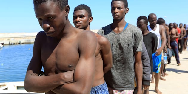 JULY 8, 2017: Illegal migrants from Africa, attempting to reach Europe, walk towards a detention center off the coastal town of Guarabouli.
