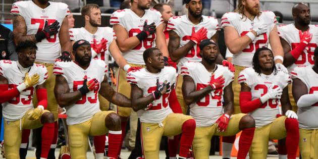 国歌演奏時に起立せず、ひざをついて斉唱を拒否するサンフランシスコ・49ersの選手ら=10月1日、アメリカアリゾナ州