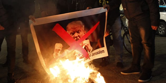 Palestinian protesters burn pictures of U.S. President Donald Trump at the manger square in Bethlehem on Dec. 5, 2017.