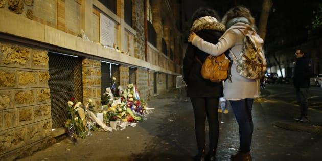 Deux personnes se recueillent devant une plaque commémorative aux abords de La Belle Équipe, à Paris, le 13 novembre 2016. REUTERS/Gonzalo Fuentes  TPX IMAGES OF THE DAY