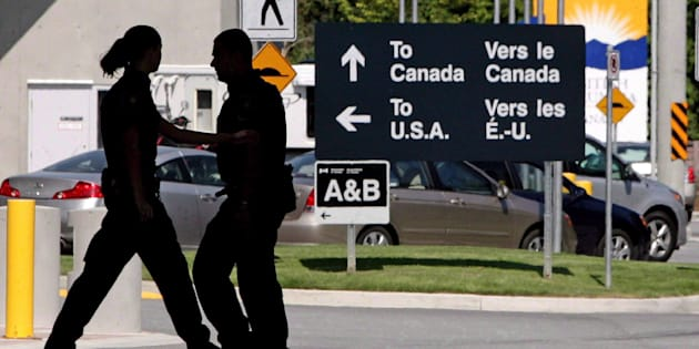 Canadian border guards are silhouetted as they replace each other at an inspection booth at the Douglas border crossing on the Canada-USA border in Surrey, B.C., on Aug. 20, 2009.
