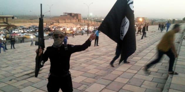 Un jihadiste du groupe État islamique porte le drapeau de l'organisation terroriste à Mossoul, en juin 2014.