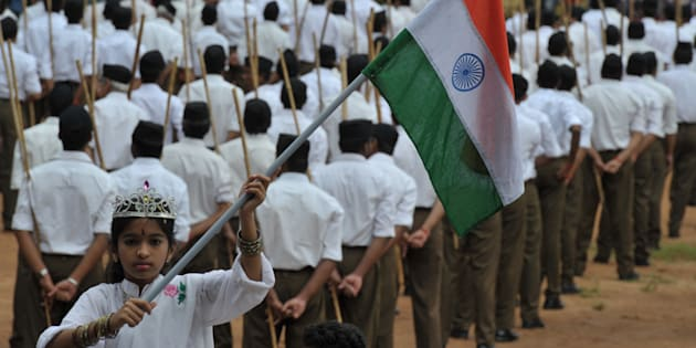 A child holding the national flag as Rashtriya Swayamsevak Sangh (RSS) volunteers line up ahead of a march in Hyderabad on October 9, 2016. NOAH SEELAM/AFP/Getty Images