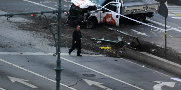 An investigator walks past a crashed pickup truck following an incident in New York on October 31, 2017.   A pickup driver killed eight people in New York on Tuesday, mowing down cyclists and pedestrians, before striking a school bus in what officials branded a 'cowardly act of terror.' Eleven others were seriously injured in the broad daylight assault and first deadly terror-related attack in America's financial and entertainment capital since the September 11, 2001 Al-Qaeda hijackings brought down the Twin Towers.  / AFP PHOTO / Don EMMERT        (Photo credit should read DON EMMERT/AFP/Getty Images)
