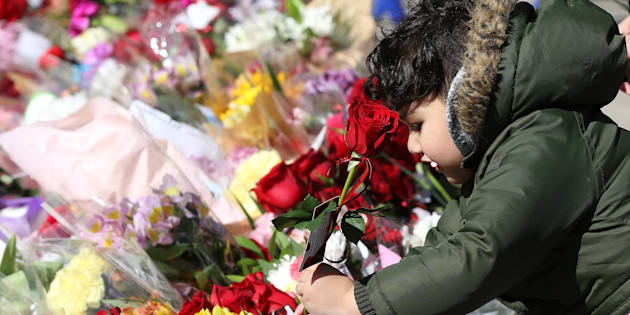 A boy leaves a rose at a memorial in Mel Lastman Square ahead of a vigil for the van attack victims, in North York, Ont. on Sunday.