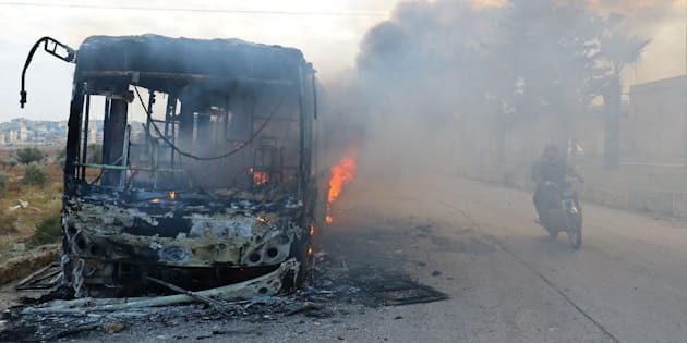 A man on a motorcycle drives past burning buses while en route to evacuate ill and injured people from the besieged Syrian villages of al-Foua and Kefraya, after they were attacked and burned, in Idlib province, Syria December 18, 2016. REUTERS/Ammar Abdullah