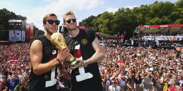 Jogadores da Alemanha, Mario Goetze e Andre Schuerrle posam com troféu da Copa em 2014.