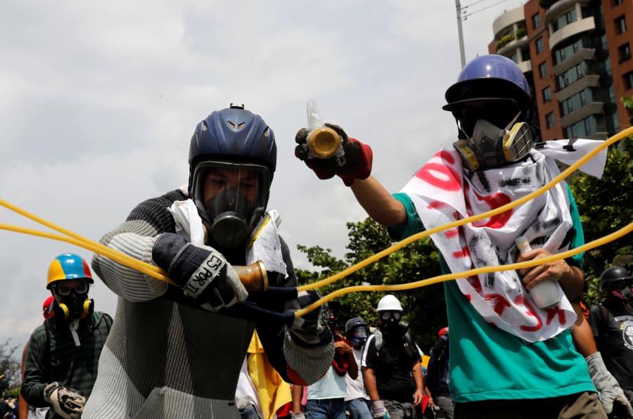 Los partidarios de la oposición usan una resortera gigante para lanzar un 'puputov', una botella llena de heces, durante una manifestación contra el presidente Nicolás Maduro en Caracas, Venezuela, el 10 de mayo de 2017.