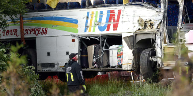A tow operator looks towards the damaged side of a tour bus that was involved in a crash on Highway 401 West, near Prescott, Ont. on June 4, 2018.