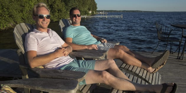 "Chris Van Lierop, right, and Tim Wisener are seen at their cottage home on Sturgeon Lake near Fenelon Falls, Ont., Wed. July 18. A growing number of Canadians are taking the term ""working remotely"" literally, leaving the hustle and bustle of city life behind to work from their cottage or winter home down south."