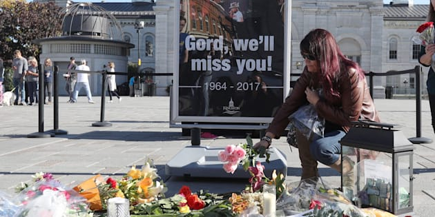 A woman places flowers at a growing memorial for the late Gord Downie, lead singer of the Tragically Hip, in Kingston, Ont., on Wednesday.
