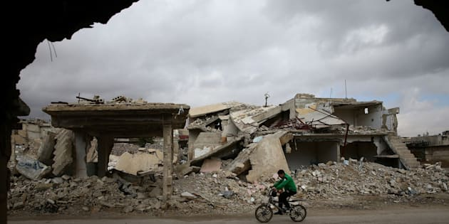 A boy rides a bicycle past damaged buildings in the rebel held besieged city of Douma, in the eastern Damascus suburb of Ghouta, Syria January 8, 2017. REUTERS/Bassam Khabieh