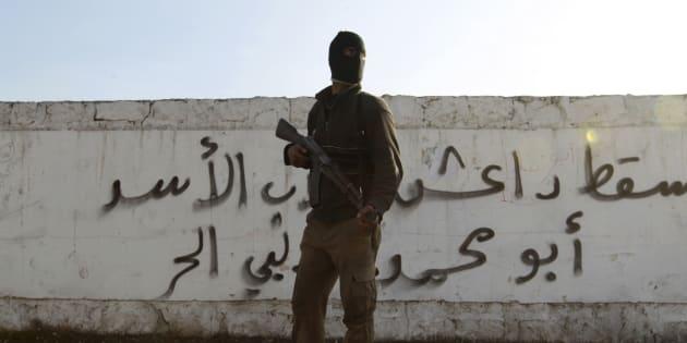 """Un soldat syrien devant un mur de graffitis où il est écrit """"Daech tombe"""", près d'Alep, en janvier 2014."""