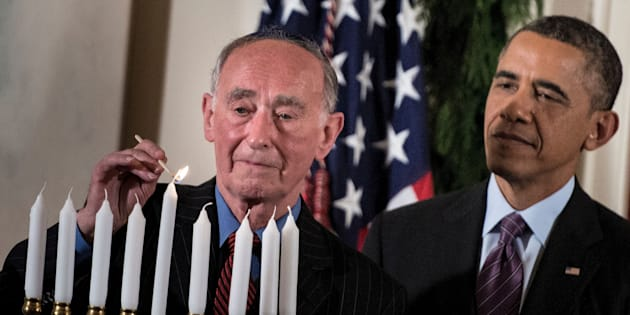 President Barack Obama watches as Martin Weiss, a Holocaust survivor, lights a menorah during a Hanukkah reception in the White House, Dec. 5, 2013.