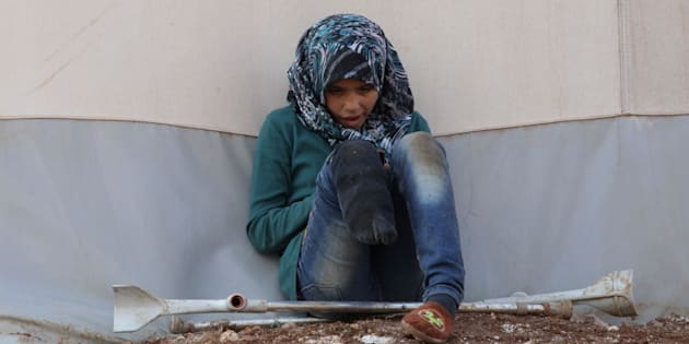 An internally displaced Syrian girl with an amputated leg checks her phone at the Bab Al-Salam refugee camp, near the Syrian-Turkish border, northern Aleppo province, Syria January 19, 2017. REUTERS/Khalil Ashawi