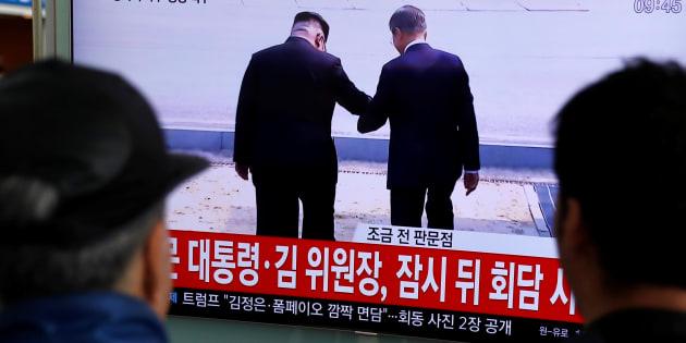 金正恩氏と文在寅氏が手をつないで軍事境界線を越える様子を生中継するテレビ番組=4月27日、ソウル